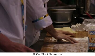 male chefs hands preparing Dough with rolling pin and added...