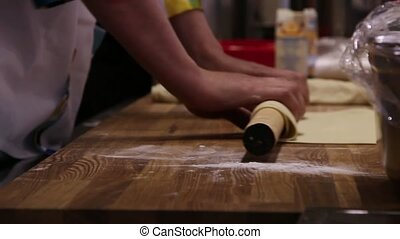 male chefs hands preparing dough with rolling pin for asian...