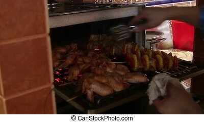 chef checks meat skewers in the oven for readiness - chef...