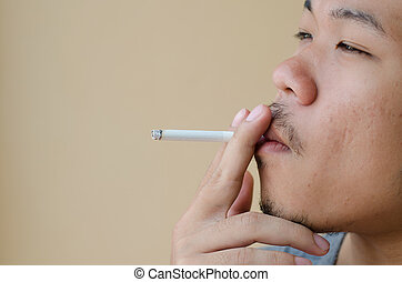 Asian young man smoking cigarette