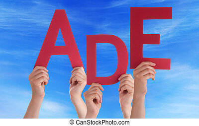 People Holding German Word Ade Means Goodbye Blue Sky - Many...