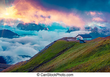 Mountain refuge in the foggy Val di Fassa valley with passo...
