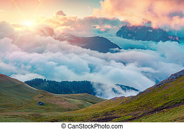 Colorful summer sunrise in the foggy Val di Fassa valley...