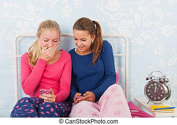 Teen girls with smartphones - Teen girls in pyjama sitting...