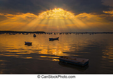 Sun rays illuminate boats in Poole Harbour - Crepuscualr...