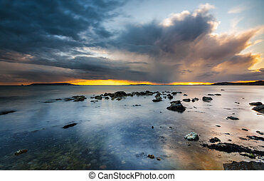 Sunset under storm clouds on the Dorset Coast - Rain-bearing...