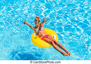 Child on inflatable ring in swimming pool. - Happy child on...