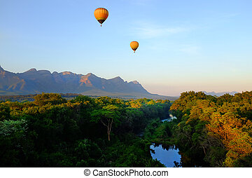 Two hot air balloons riding over african landscape.