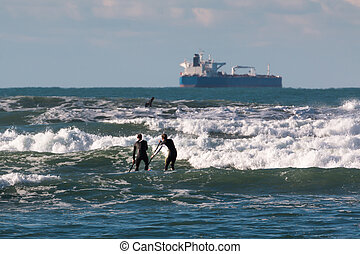 men paddleboarding on board in the waves, supply ship in...