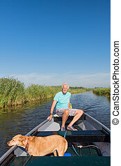 Senior man with dog in motor boat in nature