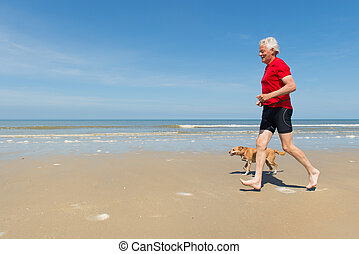 Running with dog at the beach - Senior runner with dog at...