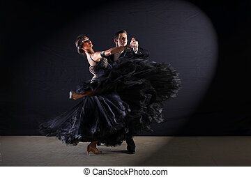 Dancers in ballroom at black background