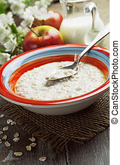 Oatmeal - Porridge and red apples on a wooden table