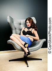seductive female - Stunning sexy woman sitting on a chair in...