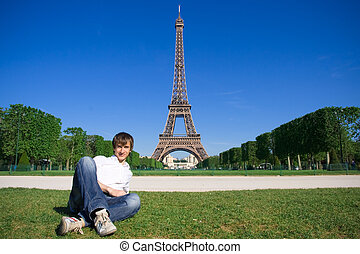 Young man lying on the Champs de Mars Eiffel tower in...