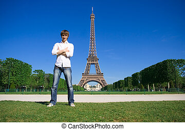 Young man standing on the Champs de Mars Eiffel tower in...