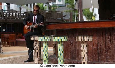 man in suit and glasses plays guitar - courageous light...
