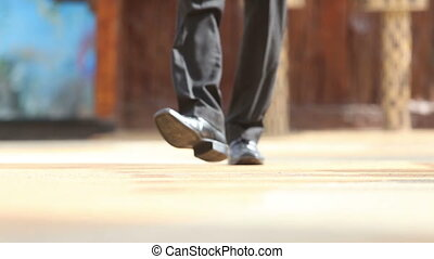 man in black shoes steps to focus and comes backward - man...