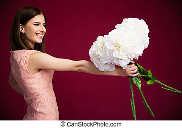 Smiling charming woman holding flowers over pink background