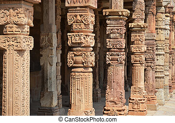 Columns with stone carving in courtyard of Quwwat-Ul-Islam...