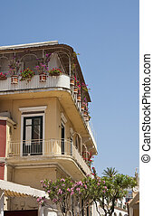 Yellow Stucco Hotel with Flowers on Veranda