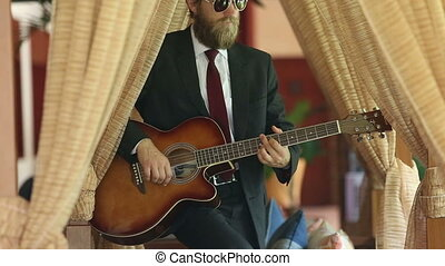 man in black suit plays guitar sensually among curtains -...