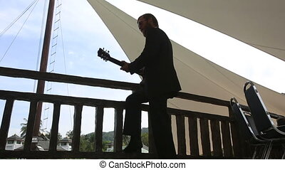 bearded man plays guitar under tent - light haired bearded...