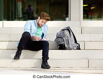 Male student sitting outside on campus reading notes -...