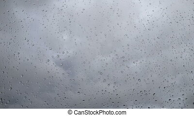 Drops on the glass in cloudy weather - Timelapse. Drops on...