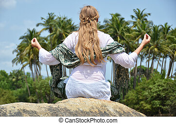 Young woman meditating on Agonda beach Goa, India
