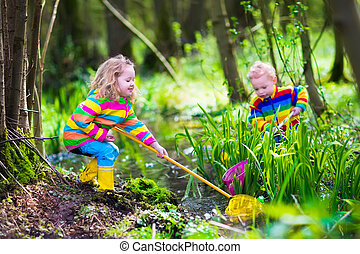 Kids playing with frog - Children playing outdoors. Two...