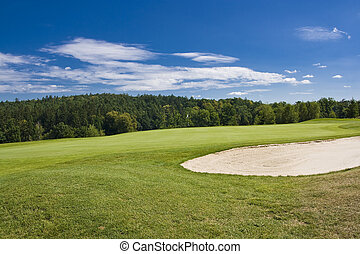 green of a beautiful golf course surrounded with bunkers...