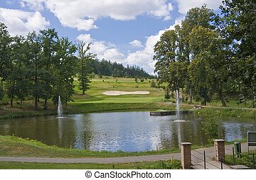 green of a beautiful golf course behind lake with dramatic...