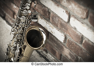 Saxophone Brick Wall - Lone old saxophone leans against...