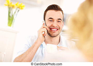 Young man talking on the phone in the kitchen