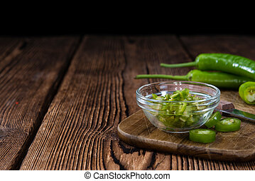 Cutted green Chilis (close-up shot) on rustic wooden...