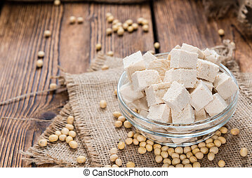 Tofu (detailed close-up shot) on wooden background