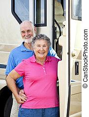 Happy Travelers - Senior couple standing in the doorway of...