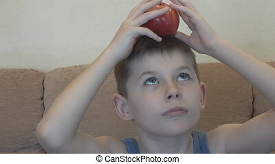 Boy balancing an apple on his head