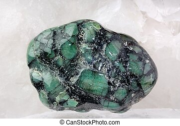 Emerald in stone on quartz background