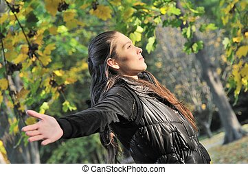 Woman enjoys sun in autumn time outdoors - Young woman is...