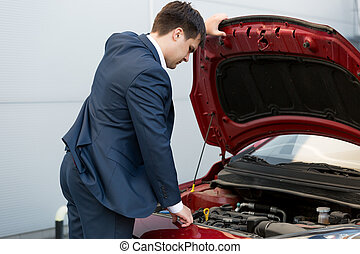 car sales manager looking under the bonnet of automobile -...