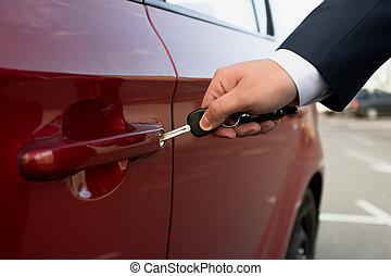 Closeup shot of businessman opening parked car with key