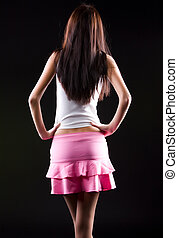 Young slim woman backside view. On dark background.