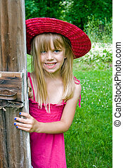 Happy Kid - Young girl peeking around an old barn dorr