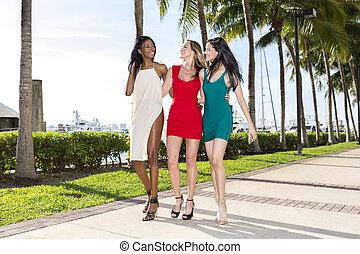Three women walking, on a warm sunny summer day. Marina with...
