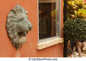 Statue of lion heads spout water.