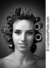 Young woman with hair rollers. Black and white portrait.