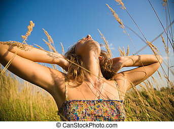 Young woman stretching up in a summer field Wide angle view...