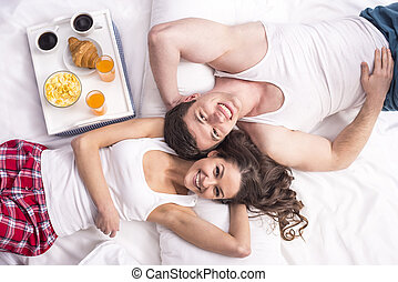 Breakfast in bed - Top view. Smiling young couple having...
